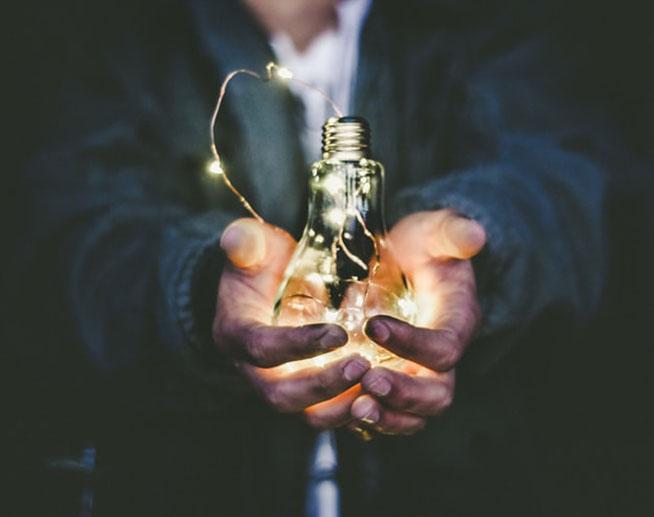 Photo illustrant une ampoule tenue entre deux mains.