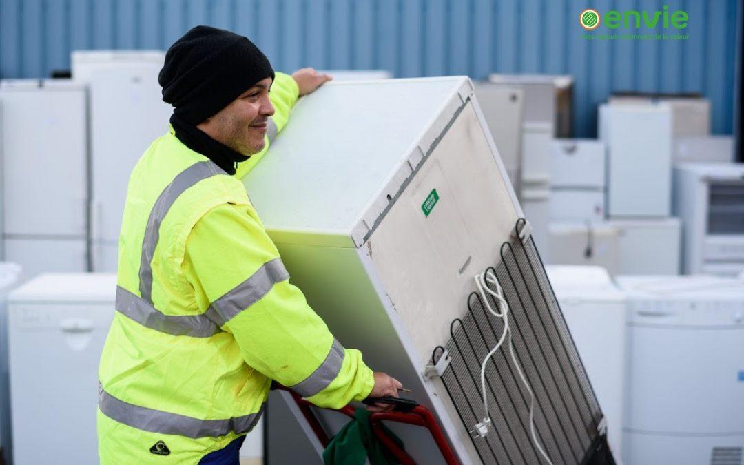 Envie : photo d'un salarié en insertion portant un réfrigérateur