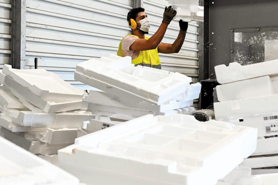 Photo illustrant un employé en train de construire des piles de polystyrène.