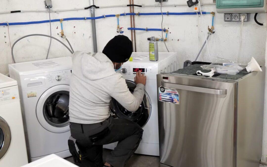 Photo illustrant l'activité d'Envie : un salarié répare un lave-linge.