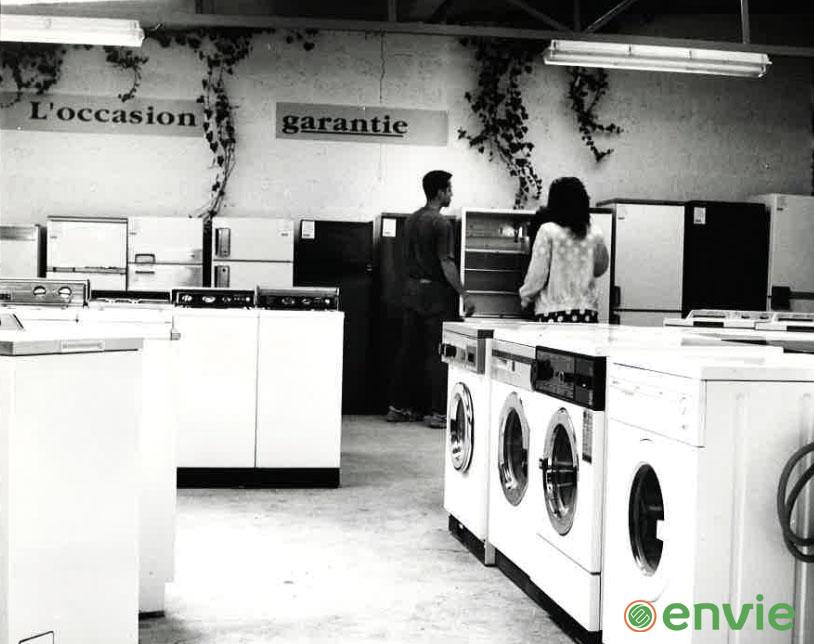 Image illustrant une rangée de lave-linges dans un point de vente Envie dans les années 80.