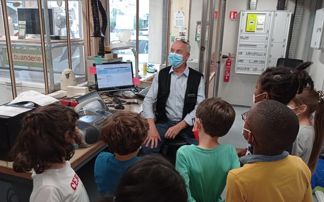 Photo illustrant un groupe d'enfants en train de découvrir l'atelier de réparation d'Envie Le Labo